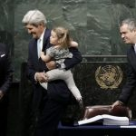 U.S. Secretary of State Kerry holds his granddaughter as he signs the Paris Agreement on climate change at United Nations Headquarters in New York