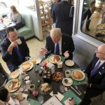 U.S. Republican presidential candidate Donald Trump talks with the media as he stops in for breakfast at Miss Katie's Diner, while campaigning in Wisconsin