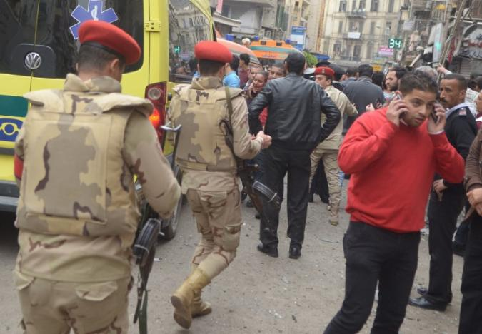Egypt army members take position as people react at a scene after an attack by a suicide bomber in front of a church in Alexandria