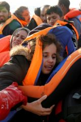 Child migrant is pulled from a wooden boat by MOAS in the central Mediterranean north of Sabratha on the Libyan coast