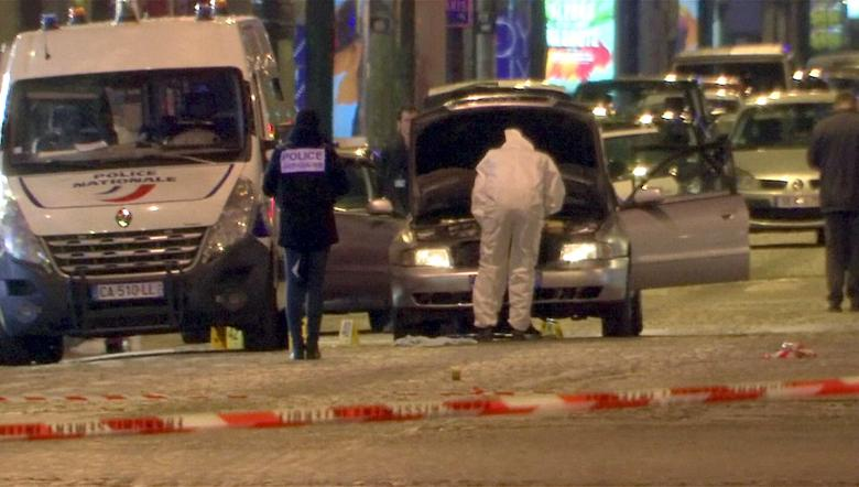 A still image from video footage shows Police investigators inspect the car used by the attacker on the Champs Elysees Avenue after a shooting incident in Paris