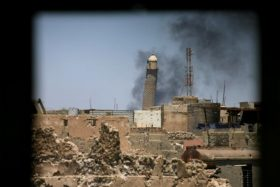 Al-Hadba minaret at the Grand Mosque is seen through a building window in the old city of Mosul