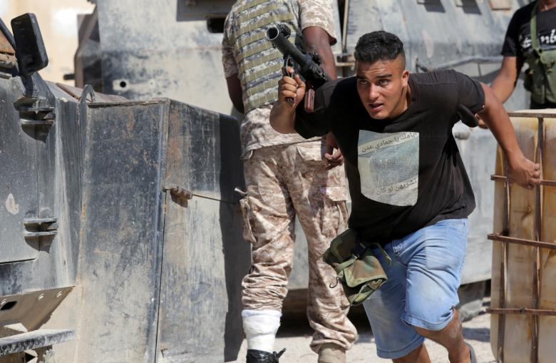 A member of Libyan National Army (LNA) runs for cover during clashes with Islamist militants in the militants' last stronghold in Benghazi