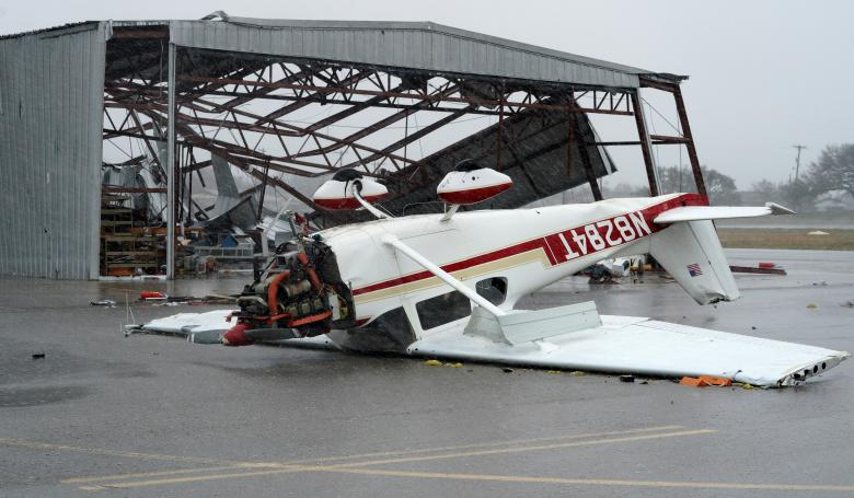 A plane lies upside down at the airport after Hurricane Harvey struck near Fulton