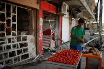 An Iraqi vendor sells vegetables outside a destroyed shop, in western Mosul