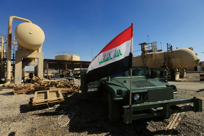 An Iraqi flag is seen on a military vehicle at an oil field in Dibis area on the outskirts of Kirkuk