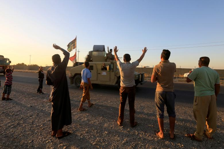 People gather on the road as they welcome Iraqi security forces members in Kirkuk