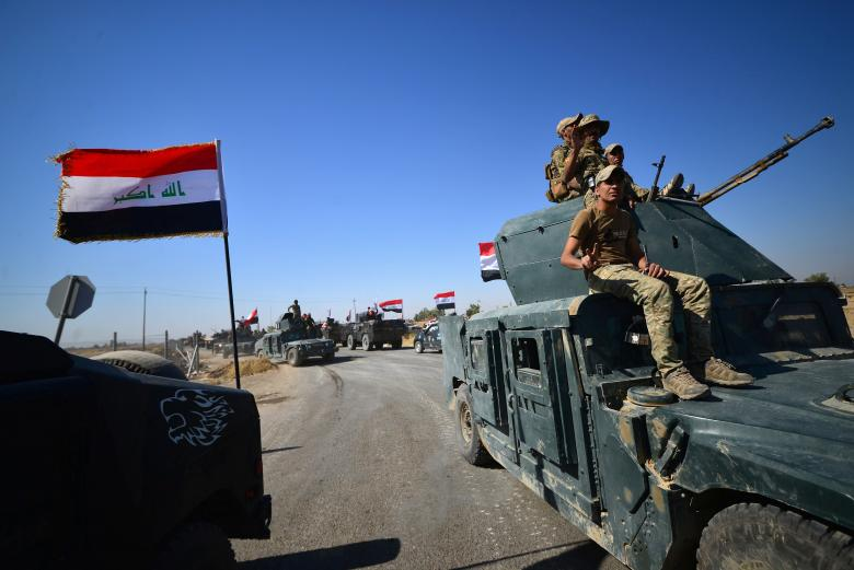 Members of Iraqi federal forces gather to continue to advance in military vehicles in Kirkuk