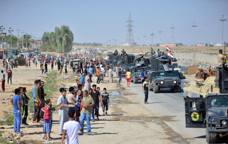 Iraqi people gather on the road as they welcome Iraqi security forces members, who continue to advance in military vehicles in Kirkuk
