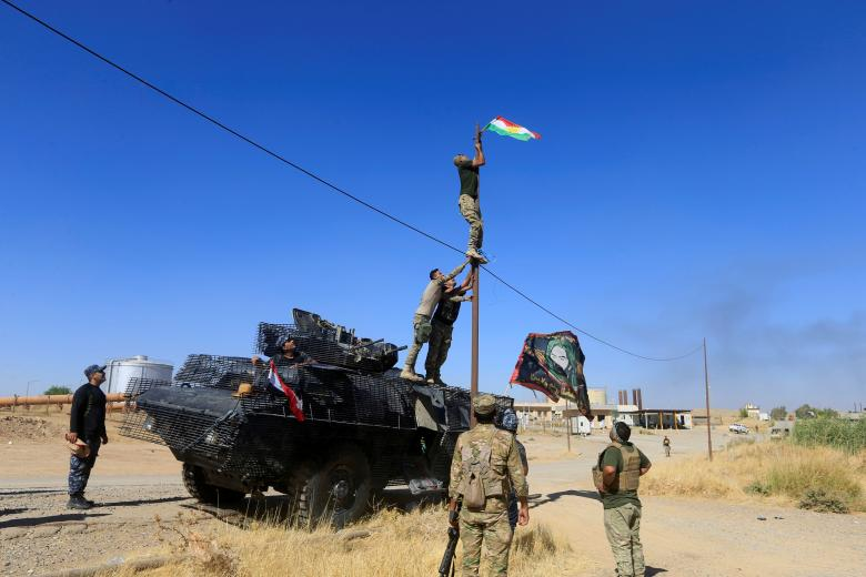 A member of Iraqi security forces takes down a Kurdish flag in Dibis area on the outskirts of Kirkuk