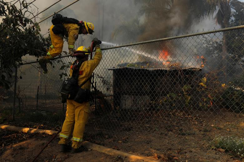 Firefighters jump a fence to try and save a burning home from the Lilac Fire, a fast moving wild fire, came through Bonsall, California