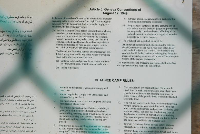 A bulletin board includes a posting on Geneva Convention rights and detainee rules at the Camp 5 high-security detention center at Guantanamo Bay