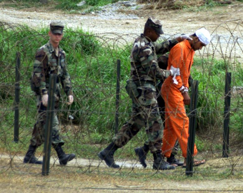 MILITARY POLICE ESCORT A DETAINEE TO AN INTERROGATION ROOM IN GUANTANAMO.