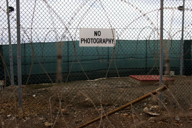 No photography signs are posted on the fence surrounding Camp Delta at the U.S. Naval Base at Guantanamo Bay