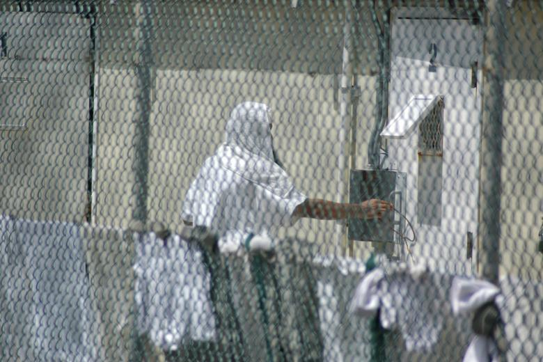 Inmate reaches near his cell at the Camp Delta detention center for terrorism suspects at the U.S. Naval Base at Guantanamo Bay