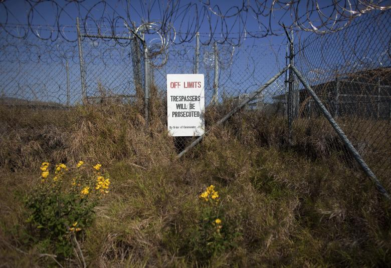 Weeds and flowers grow near the fence at Camp X-Ray, a prison formerly used to house detainees at the U.S. Naval Base at Guantanamo Bay