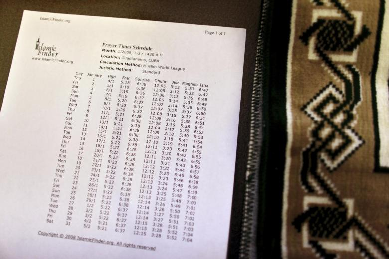 Downloaded and printed official Muslim prayer schedule sits next to prayer rug, inside cell at Guantanamo's Camp 5 detention center, at U.S. Naval Base, in Guantanamo Bay, Cuba