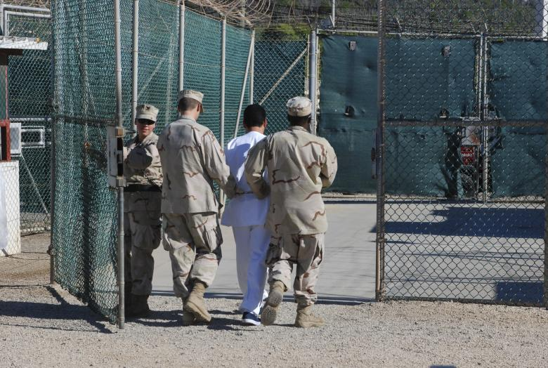 File photo of US Navy guards escorting a detainee through Camp Delta at Guantanamo Bay naval base