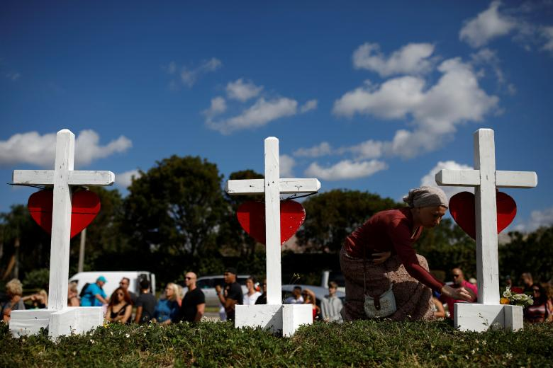 Elena Wright mourns while she puts flowers at the crosses placed in front of the fence of the Marjory Stoneman Douglas High School to commemorate the victims of the mass shooting, in Parkland
