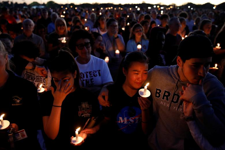 People attend a candlelight vigil for victims of yesterday's shooting at nearby Marjory Stoneman Douglas High School, in Parkland