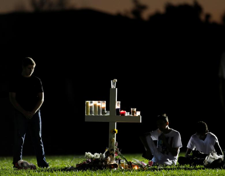 Mourners visit one of 17 crosses at a memorial for the victims of the shooting at Marjory Stoneman Douglas High School in Parkland