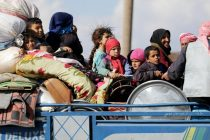 Internally displaced people ride on the back of a truck with their belongings in the town of Inab