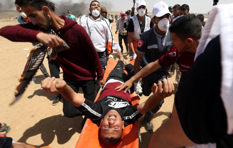 Wounded Palestinian is evacuated during a protest where Palestinians demand the right to return to their homeland, at the Israel-Gaza border in the southern Gaza Strip