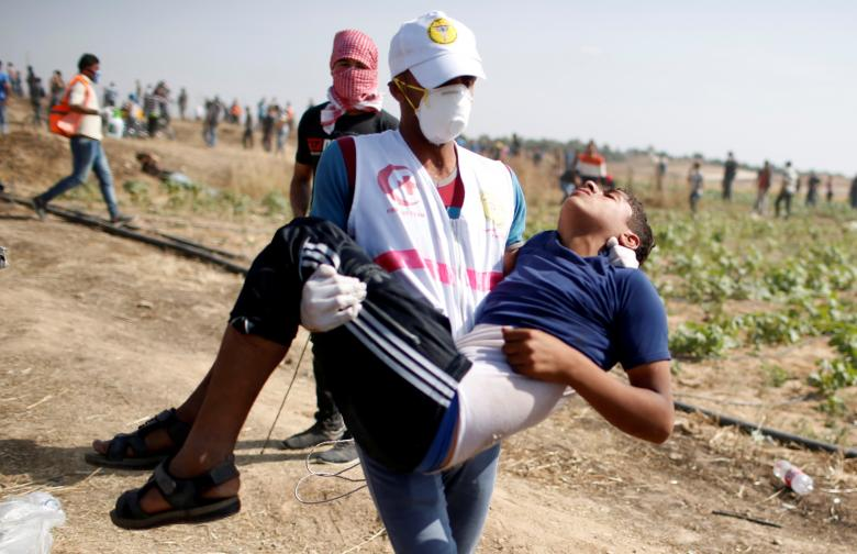 Boy is evacuated during a protest where Palestinians demand the right to return to their homeland, at the Israel-Gaza border, east of Gaza City