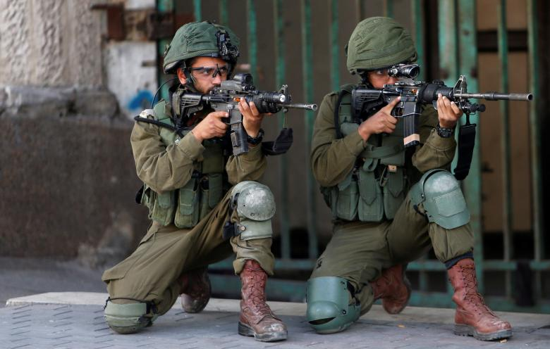 Israeli soldiers aim their weapons during a protest by Palestinians ahead of the 70th anniversary of Nakba, in Hebron in the occupied West Bank