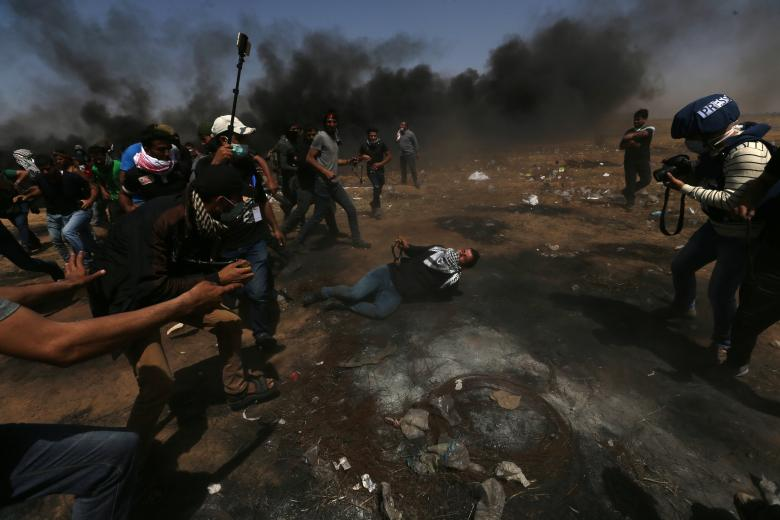 Wounded demonstrator reacts as he lies on the ground during a protest where Palestinians demand the right to return to their homeland, at the Israel-Gaza border in the southern Gaza Strip