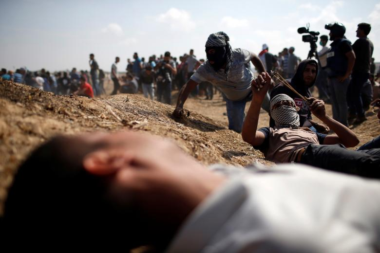 Palestinian demonstrators take cover during a protest demanding the right to return to their homeland, at the Israel-Gaza border, east of Gaza City
