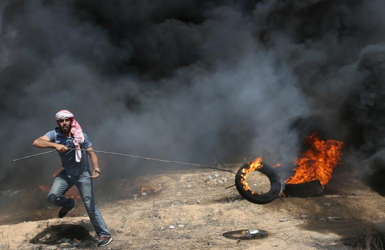 Demonstrator moves a burning tire during a protest where Palestinians demand the right to return to their homeland, at the Israel-Gaza border in the southern Gaza Strip