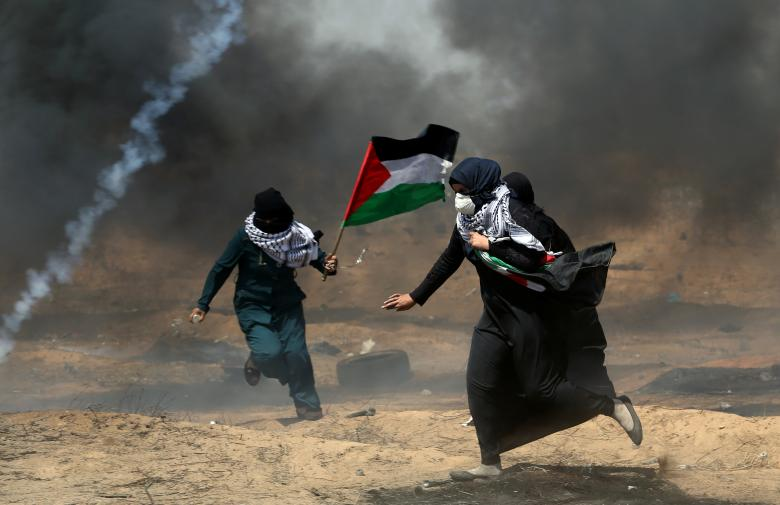 Female demonstrators run for cover from tear gas fired by Israeli forces during a protest where Palestinians demand the right to return to their homeland, at the Israel-Gaza border in the southern Gaza Strip
