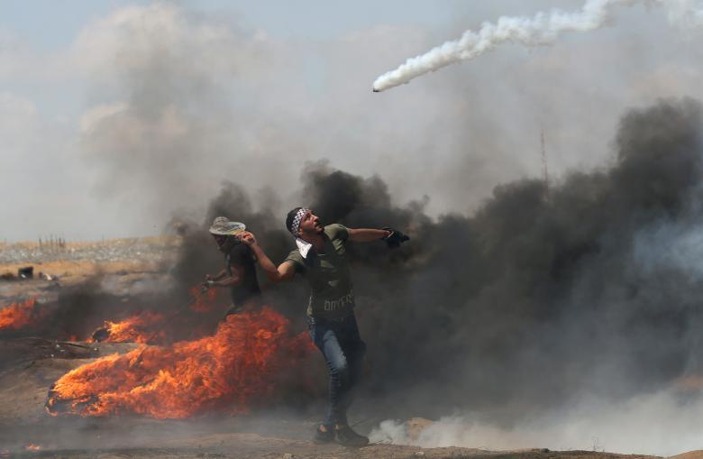 Demonstrator uses a racket to return tear gas canister fired by Israeli troops during a protest where Palestinians demand the right to return to their homeland, at the Israel-Gaza border in the southern Gaza Strip