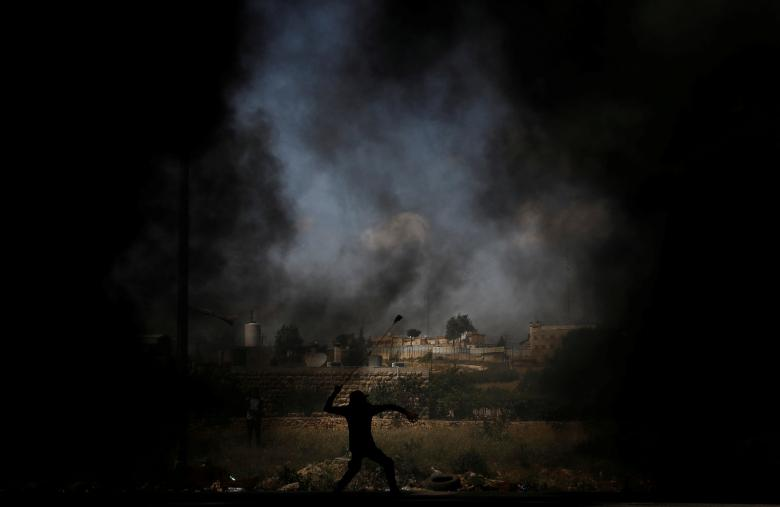 Palestinian demonstrator uses a sling to hurl stones at Israeli troops during a protest ahead of the 70th anniversary of Nakba, near the Jewish settlement of Beit El, near Ramallah, in the occupied West Bank