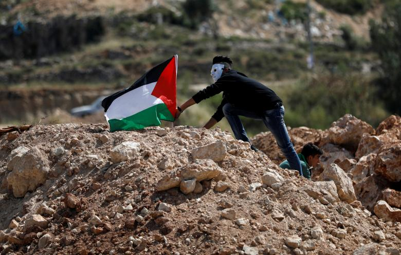Demonstrator places a Palestinian flag during an anti-Israel protest ahead of the 70th anniversary of Nakba, near the Jewish settlement of Beit El, near Ramallah, in the occupied West Bank