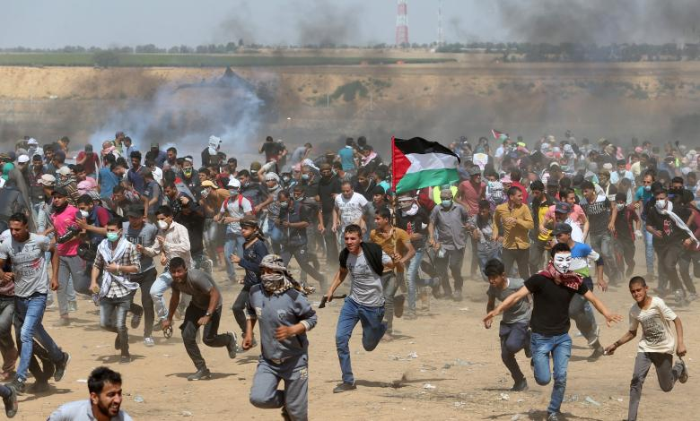 Palestinian demonstrators run for cover from tear gas fired by Israeli forces during a protest demanding the right to return to their homeland, at the Israel-Gaza border in the southern Gaza Strip