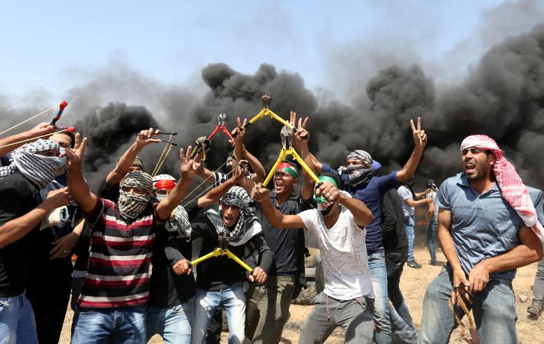 Palestinian demonstrators gesture as they hold wire cutters during a protest demanding the right to return to their homeland, at the Israel-Gaza border in the southern Gaza Strip