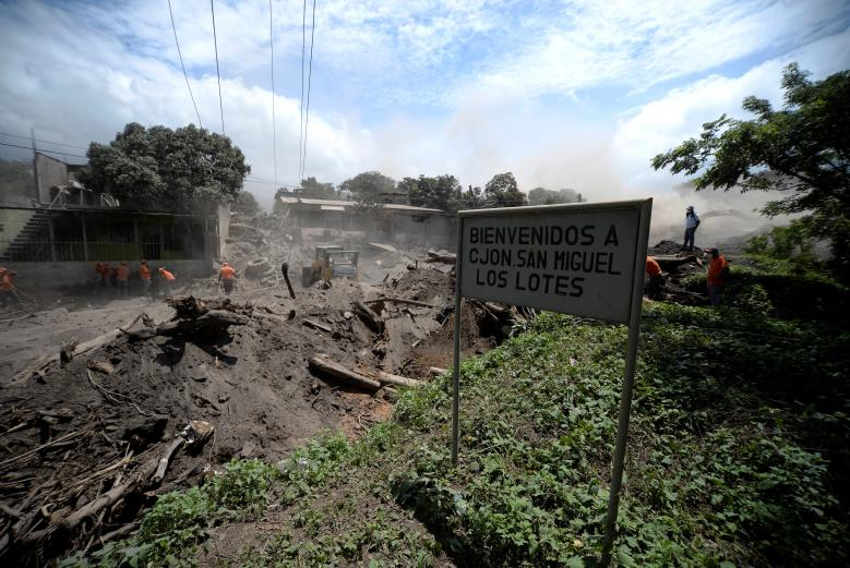 Workers remove ashes from a road at an area affected by the eruption of the Fuego volcano at San Miguel los Lotes in Escuintla