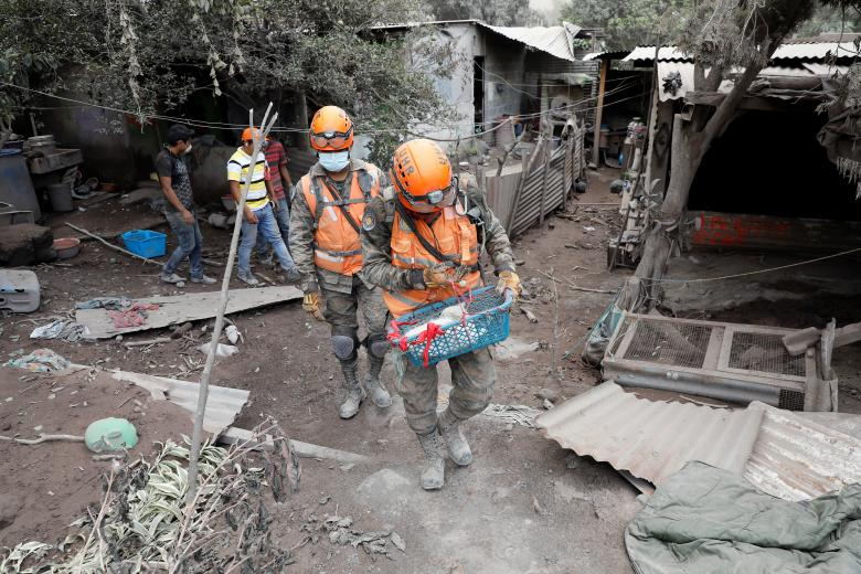 A soldier carries a cat rescued from a house at an area affected by the eruption of the Fuego volcano at San Miguel Los Lotes in Escuintla