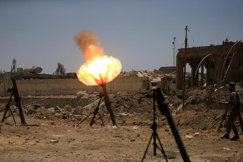 A member of the Iraqi rapid response forces fire mortar shells towards Islamic State militants during a battle with Islamic State militants in al-Zanjili neighborhood